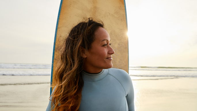 A woman stands in front of her surfboard on the beach at sunset. Surfing is great exercise for older adults.