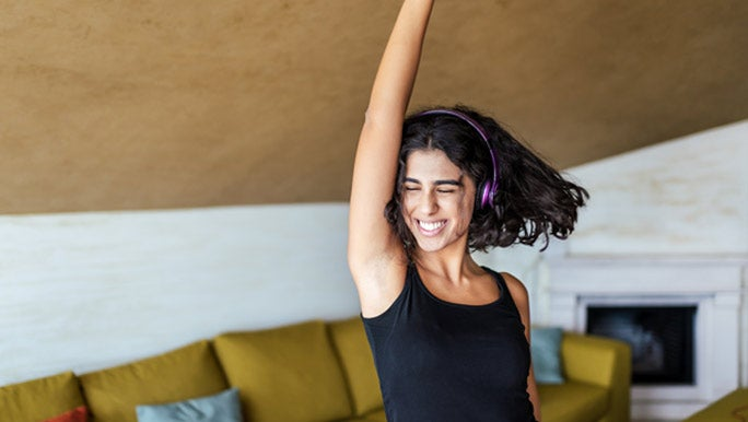 Happy young woman dancing in the lounge room