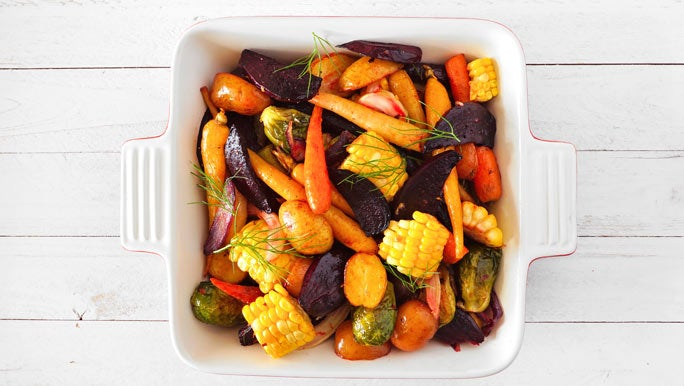 White baking dish filled with colourful roasted vegetables