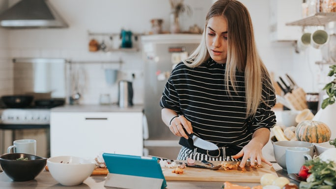 A woman is cooking in a bright, industrial-style kitchen, she is following a recipe her nutritionist gave her.