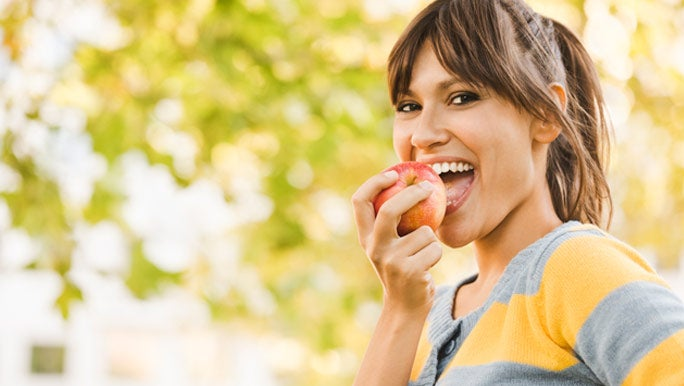 Smiling young woman eating a red apple in the park