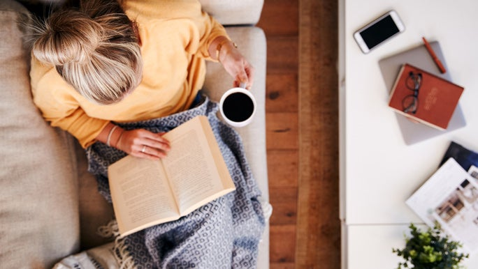 Woman relaxing on the couch at home reading a book and drinking a cup of tea