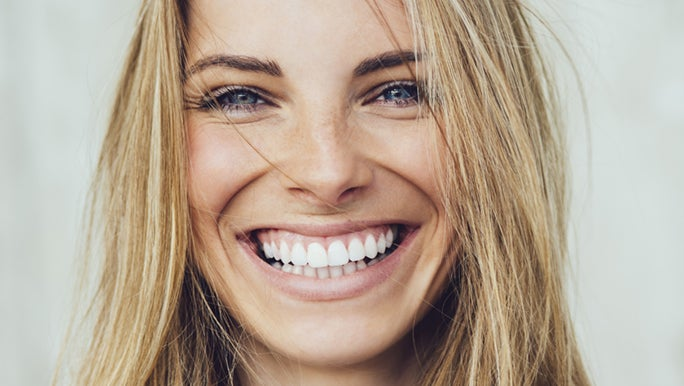 A lady with blonde hair smiles for the camera. She is enjoying the benefits of quitting sugar.