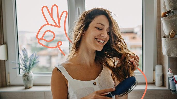 Smiling woman brushing her long brown hair