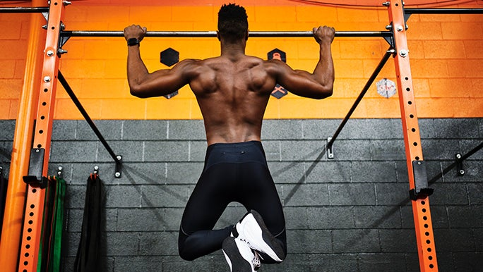 From behind, a muscly man is doing chin ups on a bar in front of a yellow and black wall, in the hopes of bulking up.