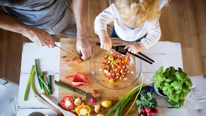 From above, a father and his toddler prepare a chopped salad. Cooking is a good way to introduce foods to picky toddlers