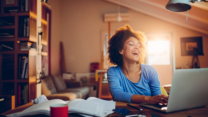 A woman in a home office throws back her head and laughs, it looks as though she is taking a study break to chat to a friend on her laptop.