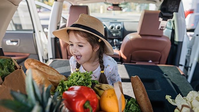 A toddler is in the boot of a car, excitedly looking at a box full of veggies.