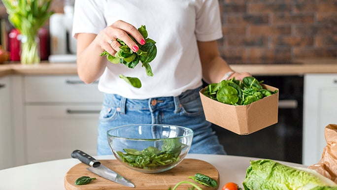 The torso of a lady is in the frame. She is standing in a kitchen and transferring raw vegetables from a cardboard box into a glass bowl.