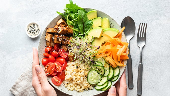 From above, two hands hold a plate that is piled with healthy food.