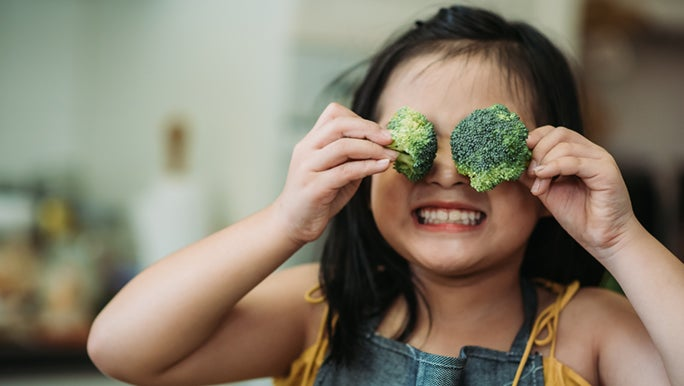 A little girl is holding broccoli in front of her eyes and smiling. She is choosing healthy food over junk food.