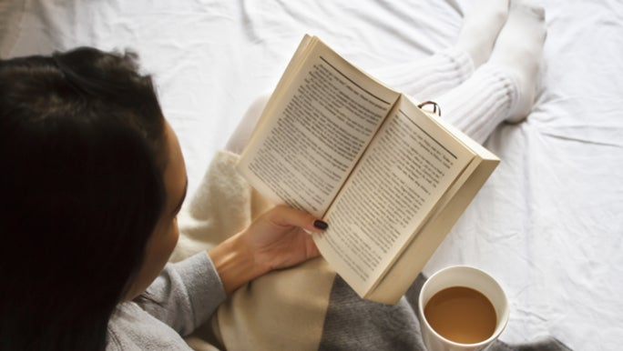 A woman is reading a book in bed with a cup of tea in her hand. She is avoiding screen time as it affects her sleep.