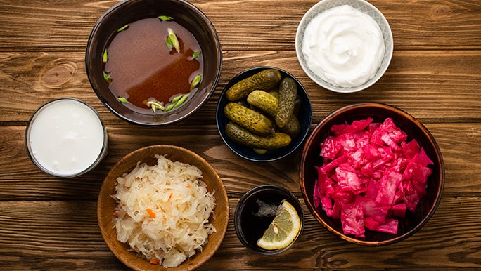 From above, a bunch of bowls containing fermented foods are on a table. They are all rumoured to promote healthy gut flora.