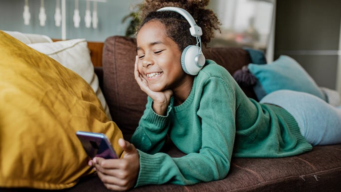 Smiling girl lying on the couch watching videos on a smartphone