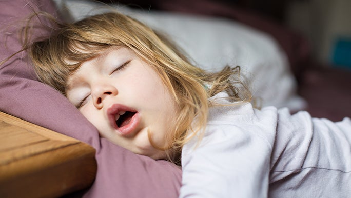 A close up of a sleeping toddler. Her mouth is open suggesting that she is snoring.