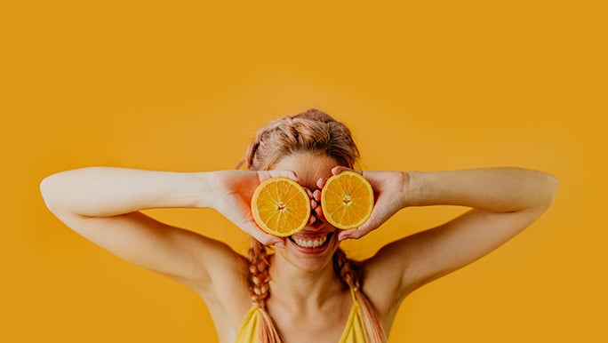Standing in front of an orange wall, a lady with orange hair holds up two halves of an orange in front of her eyes.