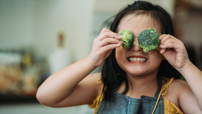 Happy little girl holding broccoli florets over her eyes