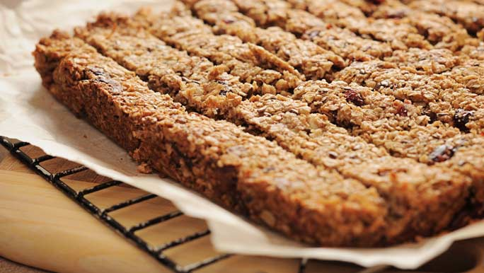 Healthy homemade muesli bars cooling on a wire rack and baking paper