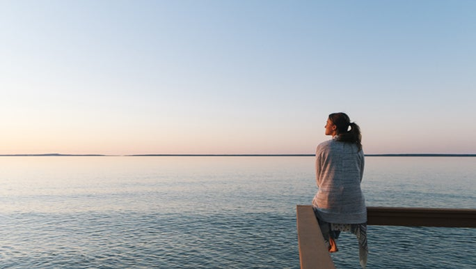A lady perches on a handrail in front of the ocean. She is staring at the sunset looking for her motivation.