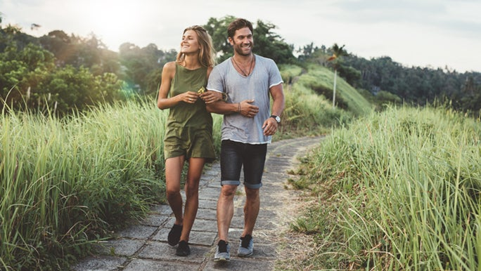 A couple happily walks along a path, they are enjoying the health benefits of walking.