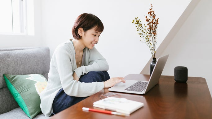 Woman working from home on her laptop at the coffee table