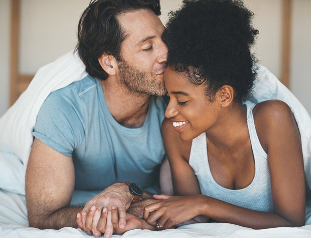 Man lying in bed with his partner kissing her affectionately on the forehead