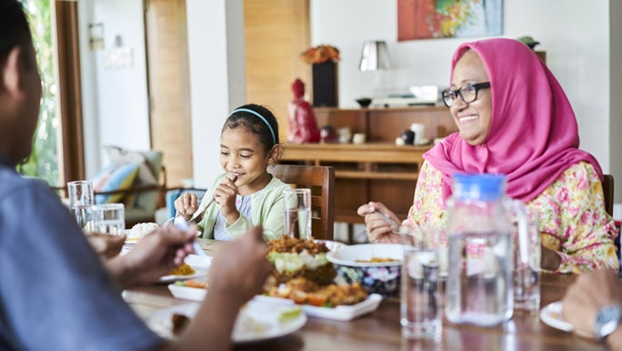 A family sits down to dinner, the woman is wearing a pink scarf around her hair and the little girl is smiling and eating happily.