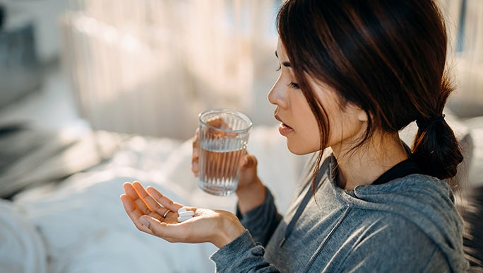 Woman with two pills in one hand and a glass of water in the other, she is trying to remember if she took her medication.