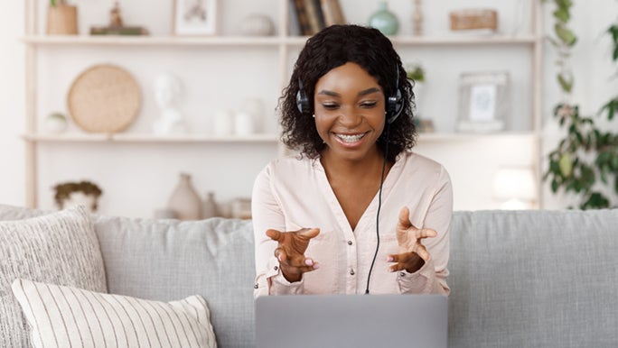 A life coach sits on a lounge, she is smiling and explaining to a client different strategies they should try. She has her hands out as if caught mid-sentence.