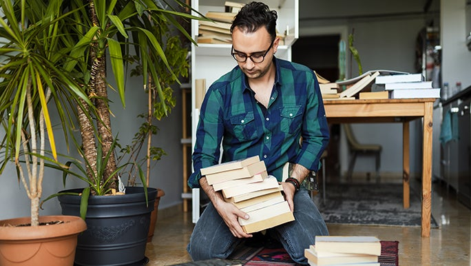 A man is sitting on the ground organising his book collection while stuck at home bored.