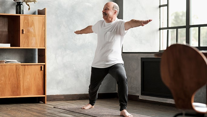 A man does Yoga in his home, he is wearing track pants, a t-shirt and no shoes.