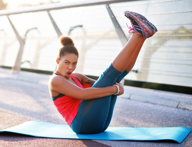Dark-haired woman making funny face while doing yoga on sport mat outside