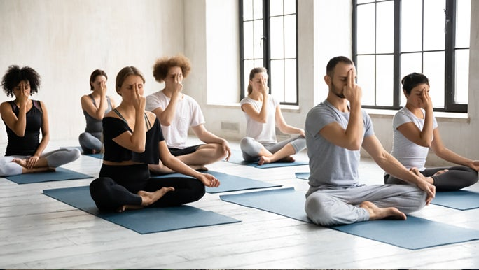 In an exercise class, seven people are experiencing the benefits of meditation and mindfulness.