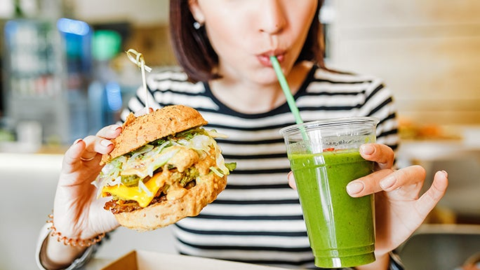 A lady holds a burger in one hand and a green smoothie in the other. It's called balance.