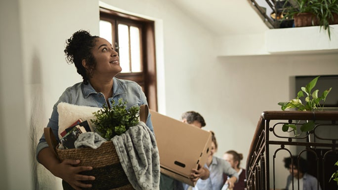 A family is walking up stairs carrying baskets and boxes in a light-filled building. They seem excited about moving house.