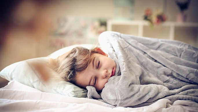 A child snoozes under a weighted blanket.