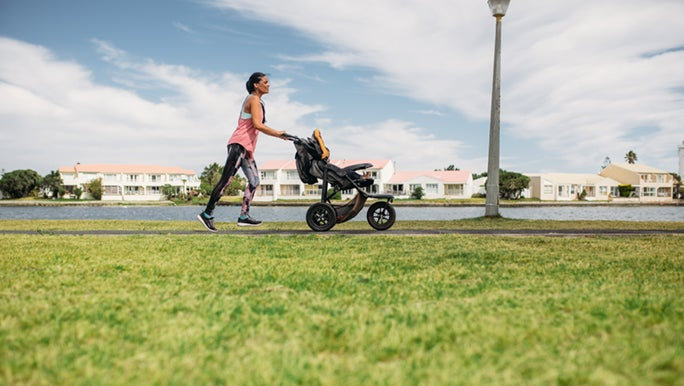 A woman is enjoying the benefits of jogging with her child in a pram.