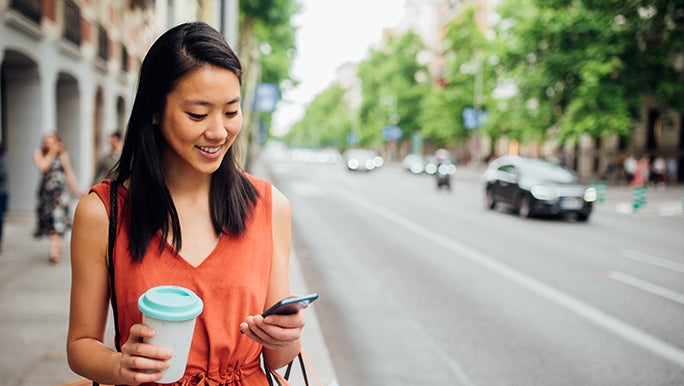 A woman smiles and looks at her phone, she has a coffee in one hand and looks to be taking a work-life balance break.