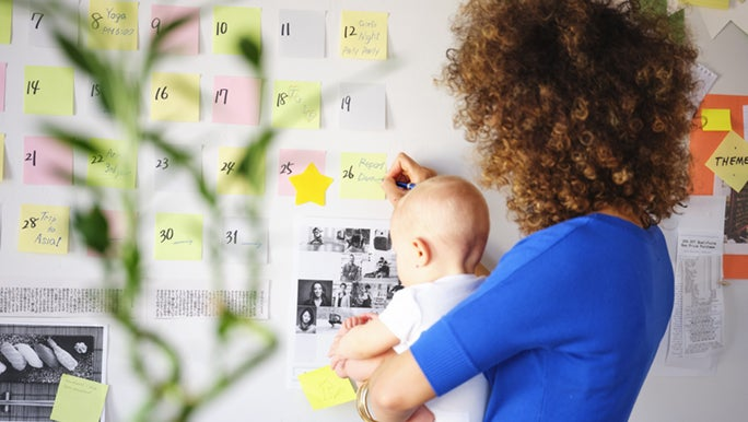 From behind, a woman holds a baby while writing on colourful Post-it notes that are stuck to the wall.