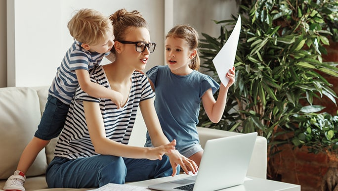 A mother works on a laptop as her two children climb all over her, she looks stressed.