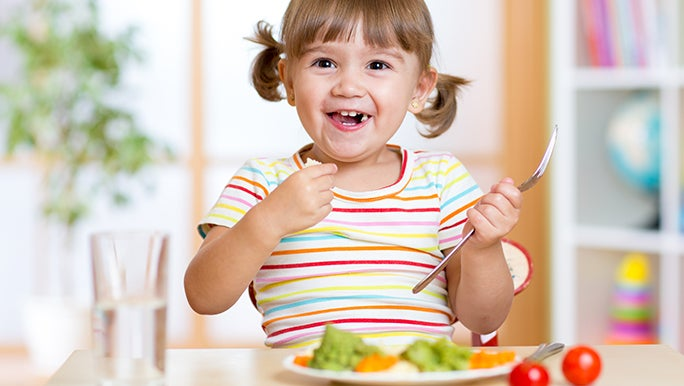 A girl with a fork-in-hand is happily eating some vegetables which is part of her daily fruit and vegetable nutrition.