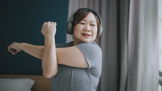 Lady wearing headphones stretching before exercise to prevent muscle injuries.