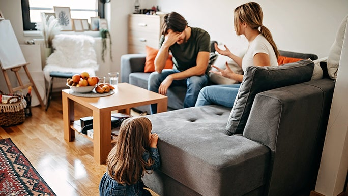 A couple argues on a couch as a child sits on the ground watching. There is a lot of relationship conflict in the picture.