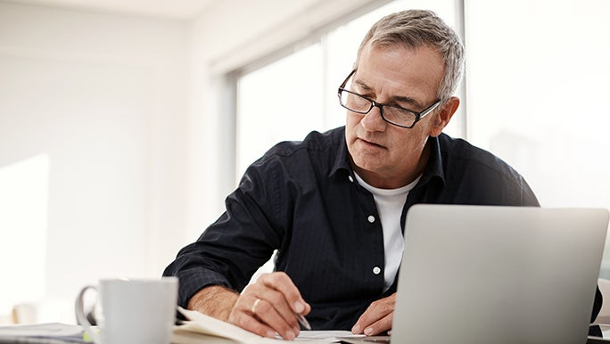 A man in glasses is concentrating on some notes he is taking. There is an open laptop in front of him, he looks deep in thought.