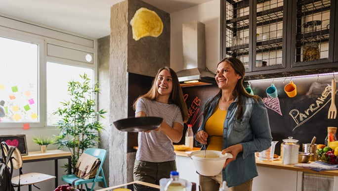 A teenager is flipping a pancake in the air, her mum watches on with an entertained look on her face.