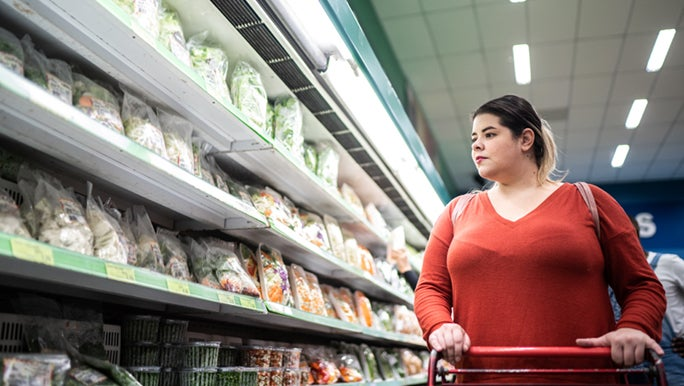A gorgeous woman shops for vegetables, hopefully, she knows that fad diets don't work.