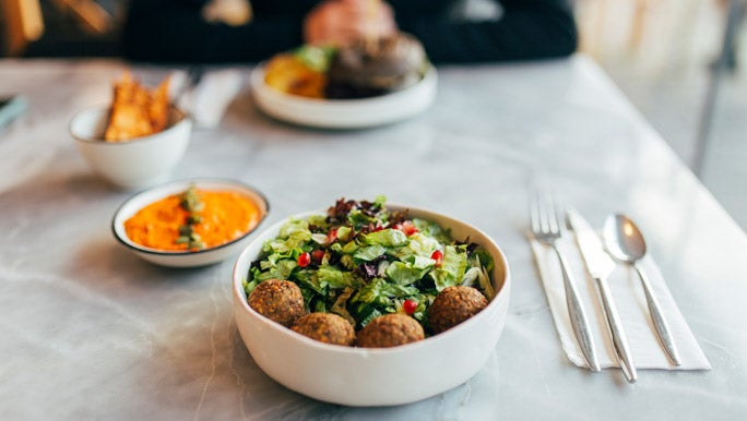 A falafel bowl with fresh green salad and carrot dip on a restaurant table