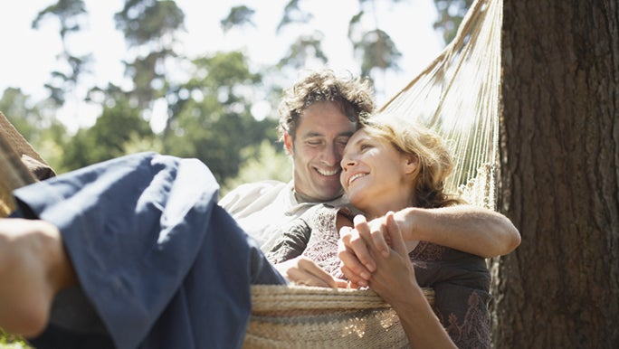 A couple are relaxing together in a hammock. They are still young but thinking about healthy ageing.