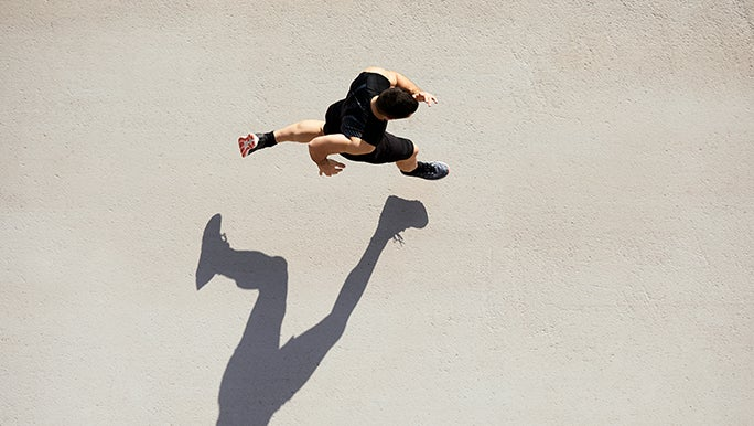 From above, a man runs on a concrete floor, both of his feet are off the ground so his shadow isn't connected to him. It's an impressive photo composition.