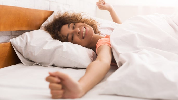 Woman waking up refreshed in the morning stretching in bed